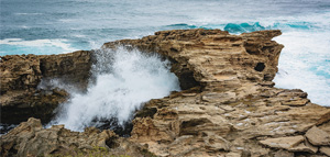 Waves crashing over rocks at The West End of Rottnest Island